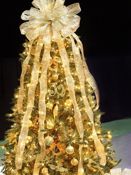 Glittery Gold Christmas Tree  Not all that glitters is gold. White lights, glittery cursive Christmas-word ornaments, and gleaming ornament balls make this decadent Christmas tree glow from within. Top with an oversize, shear bow with cascading tails for extra glamour.