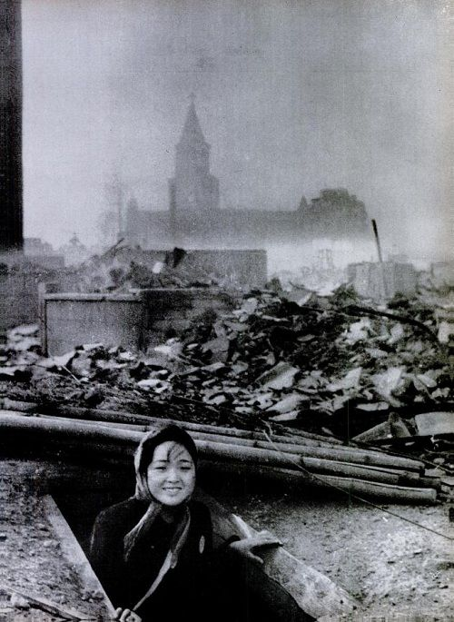 A girl emerges from a bomb shelter surrounded by the ruins of Nagasaki - August 10, 1945.: