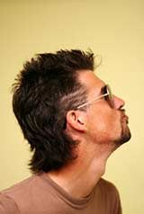 Man with a 80s mullet hairstyle with shaved lines on side of head.