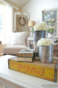 Living Room decor - rustic farmhouse style. Coffee table styling vignette with old coca cola box, flour sifters and books.