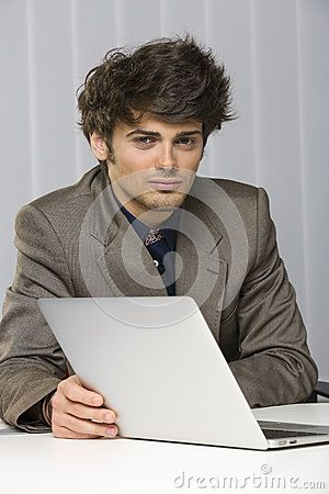 Portrait of handsome young business man looking at the camera and smiling confidently while working at his laptop.  Download Handsome Young Business Man Stock Photography for free or as low as 0.69 lei. New users enjoy 60% OFF. 19,865,028 high-resolution stock photos and vector illustrations. Image: 29509862