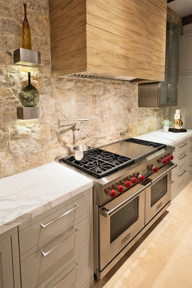 """Trendy Kitchens. This kitchen incorporates an interesting wood hood over the 60"""" Wolf Dual Fuel Range plus unique lighting anchored on a natural tumbled stone wall. Designer Courtney Lawrence Ziething, CC and Company, Newport Beach, Calif. Photo courtesy of Sub-Zero/Wolf."""