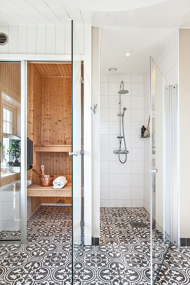 gorgeous bathroom with mosaic tile flooring, white walls, and sauna