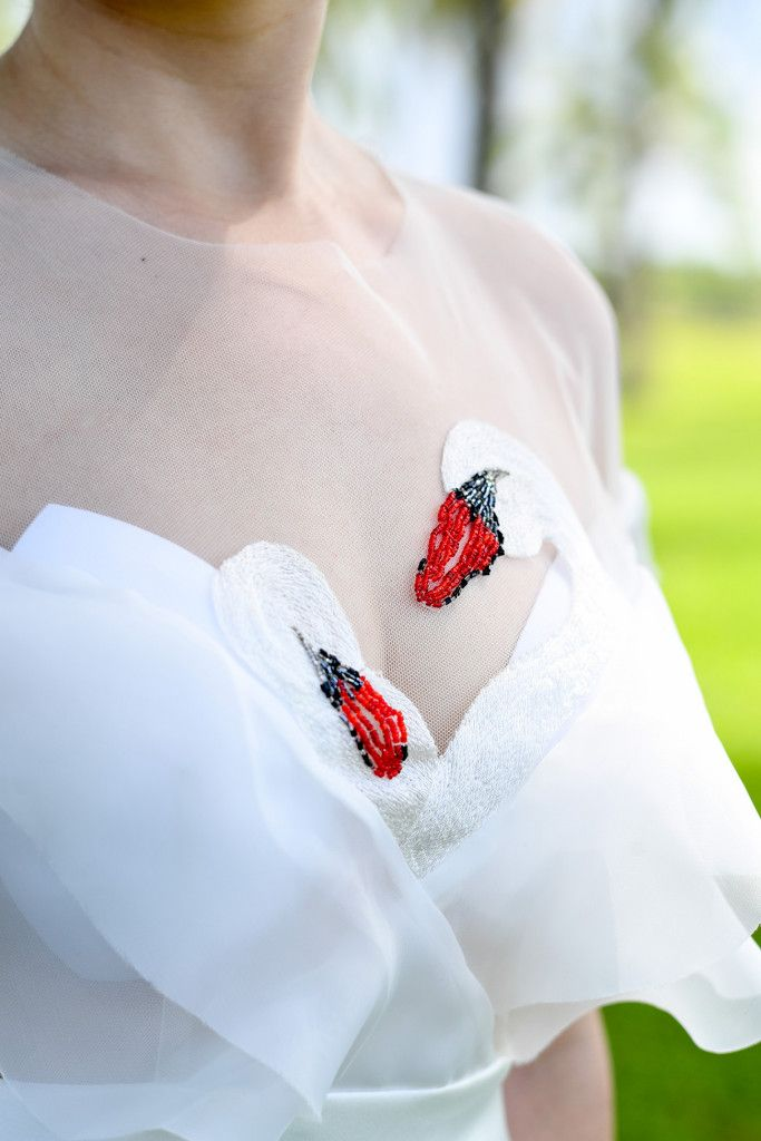 Detail on the front of the bride's wedding dress with swans made of pearls