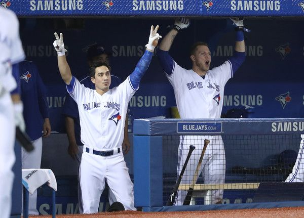 Darwin Barney #18 and Michael Saunders #21 celebrate in the dugout after Russell…