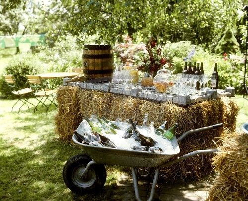 Hay bale serving table and drinks that are actually kid level in a wheel barrow ...love.  Wheel barrow for beer, water?