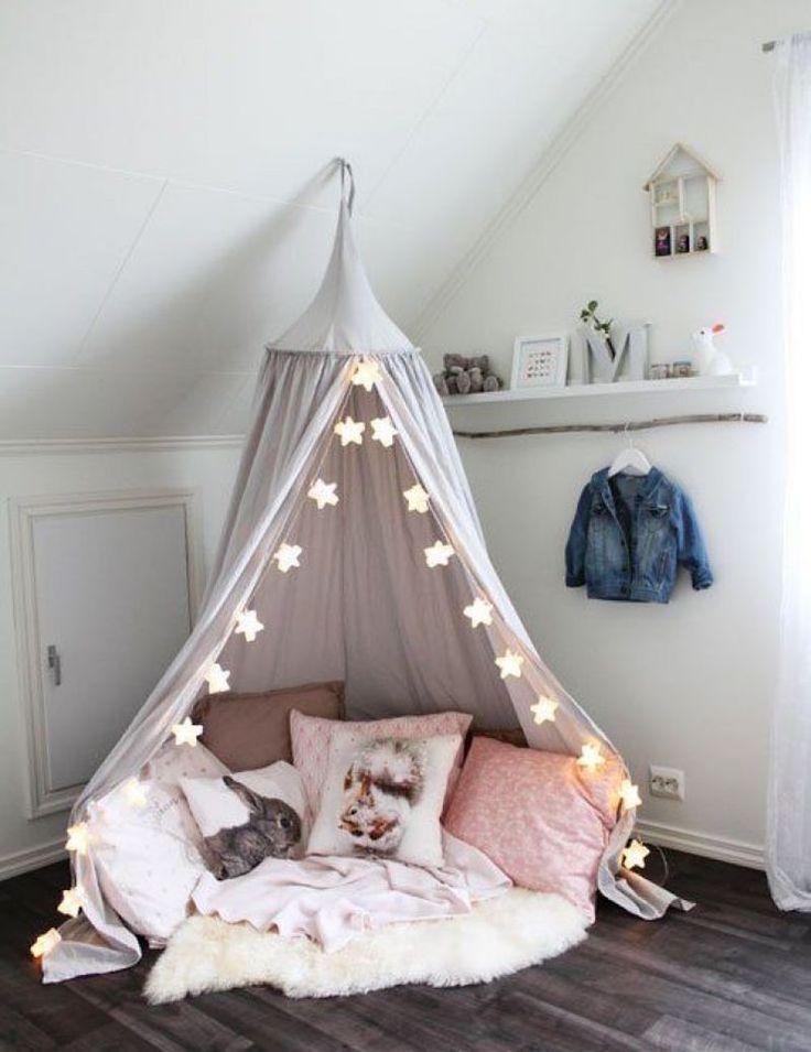 coin lecture enfant dans la chambre fille -ciel de lit suspendu et guirlandes étoiles