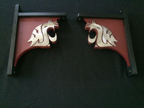 """Washington State University rustic shelf brackets.   Metal WSU Logo on both sides of brackets  15 1/4 tall x 9 1/4 wide x 3/4 thick The paint is color matched to WSU colors and clear coated.  Each bracket is Approx, 15 1/4 tall x 9 1/4 wide x 2 1/4 thick Mounting hardware not included. Material: 3/4"""" furniture grade plywood & 1/8 metal WSU  At this time we can ship WITHIN 15 days. We ship USPS mail and send you the tracking number"""