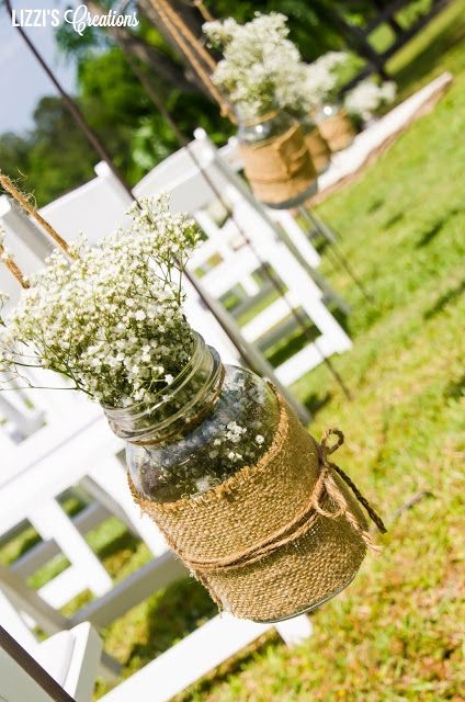 Baby's breath in a hanging mason jar with burlap and jute twine..... Perfect for a rustic, country wedding isle...