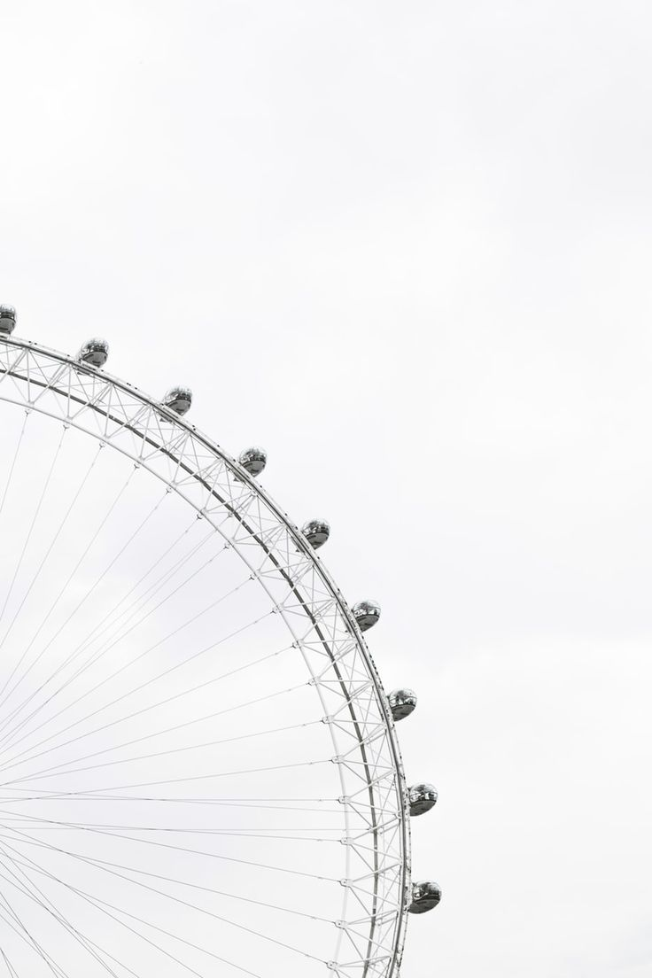 Part of a ferris wheel with enclosed cars for riding in ...
