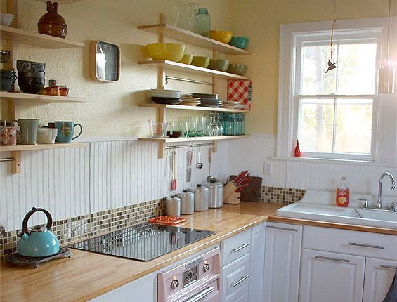 White cabinets, butcherblock countertops, open shelving, vintage farmhouse sink