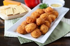 Savory ham and cheese, spiced with bits of ground red pepper and dry mustard, are shaped into balls and fried until crisp and brown. Serve these appetizers warm.