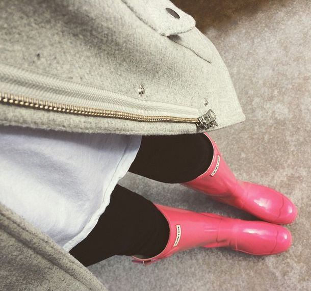 White tee, tan coat, leggings, and bright pink Hunter boots