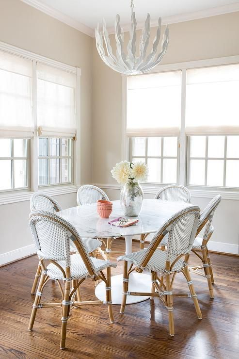 Illuminated by a glossy white leaves chandelier, an Oval Saarinen Dining Table is surrounded by Serena & Lily Riviera Side Chairs placed in front of windows dressed in white linen roman shades complementing beige painted walls in this gorgeous breakfast room.
