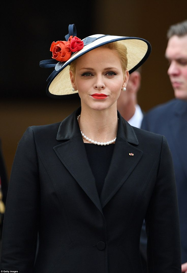 Wearing all black but with a statement hat with red flowers Princess Charlene has once aga...