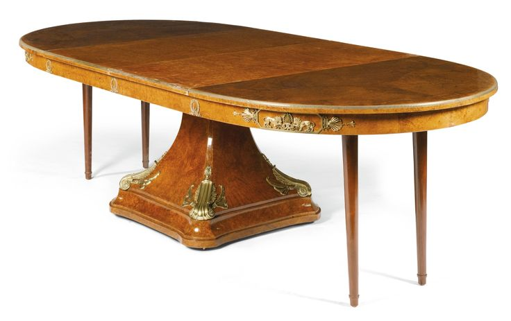 A GILT-BRONZE-MOUNTED THUYA WOOD DINING TABLE, IN EMPIRE STYLE with an oval gilt-bronze banded top, the frieze mounted with ribbon tied acorn and oak leaf wreaths flanked by a tablet with canted corners enclosing two lions flanking a stylised anthemion with two folding later turned tapering legs on a central pedestal with concave sides and a boldly scrolled lotus leaf on each corner on castors, the hinge on the table stamped BJSCDG.V.F à Paris; together with two leaves 75cm. high, 266cm…
