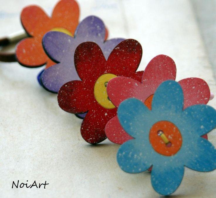 Gumička. Ozdobená dreveným kvetom - maľovaným gombíkom.Využiť sa dá ako ozdoba na ruku, do vlasov, ale aj na pohár či vázu.Možnosť vyrobiť aj v iných veľkostiach a farbách.