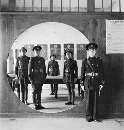 The Chinese Police Force; the Assistant Chief of Police and his staff grouped in a circular doorway at headquarters in Chengtu.  Beaton Cecil  © IWM (IB 2439C)