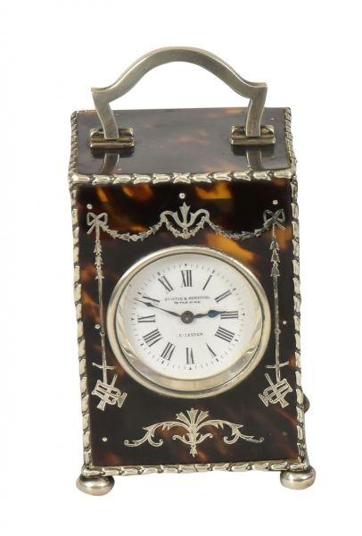 """CURTIS & HORSPOOL. Raro carriage clock inglês com caixa em casco de tartaruga polido marchetado no estilo neoclássico. Base e guarnições em prata do período """"Edward VII"""", contraste da cidade de """"Londres"""" de 1906. Mostrador esmaltado com designação do fabricante """"Curtis & Horspool to the King - Leicester"""". Alt.: 9,5cm. Larg.: 6cm. Prof.: 5,5cm. Prateiro """"W.C"""". Base R$500,00. Dez16. Vendido por R$750,00."""
