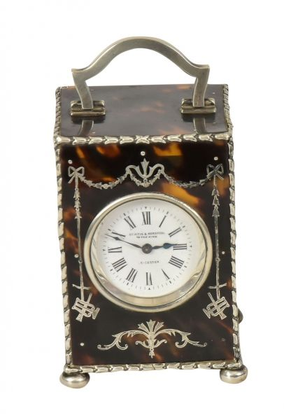 """CURTIS & HORSPOOL. Raro carriage clock inglês com caixa em casco de tartaruga polido marchetado no estilo neoclássico. Base e guarnições em prata do período """"Edward VII"""", contraste da cidade de """"Londres"""" de 1906. Mostrador esmaltado com designação do fabricante """"Curtis & Horspool to the King - Leicester"""". Alt.: 9,5cm. Larg.: 6cm. Prof.: 5,5cm. Prateiro """"W.C"""". Base R$500,00. Dez16"""