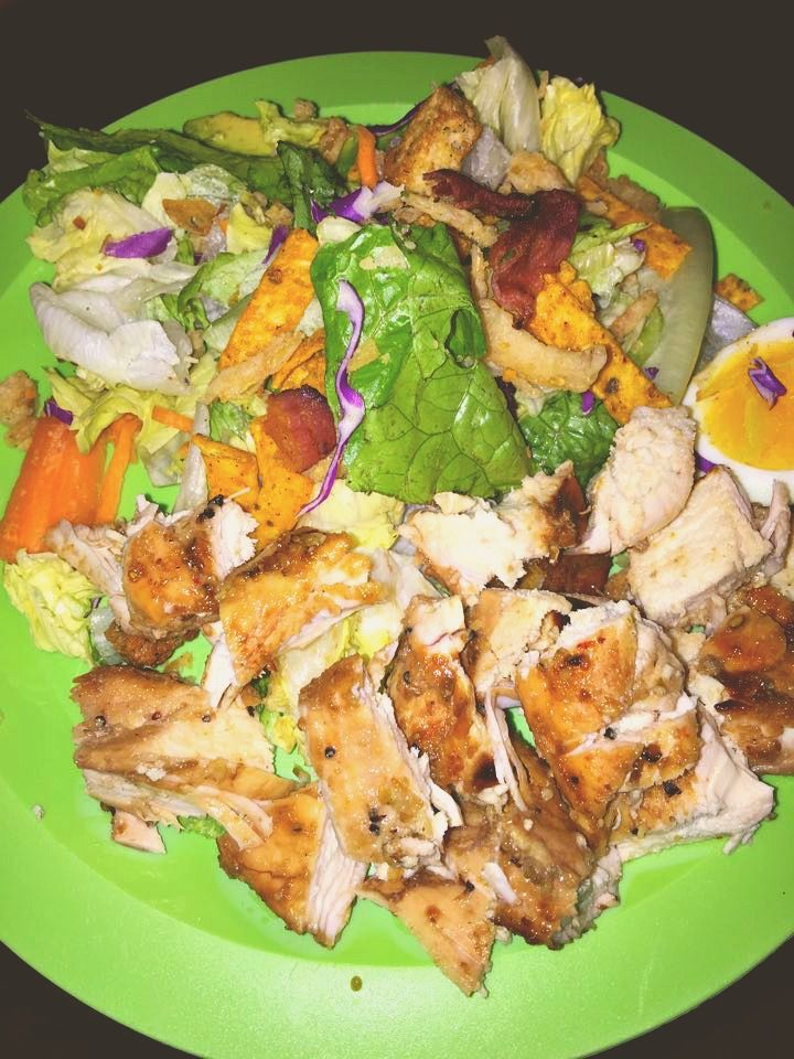 grilled chicken salad with soft boiled eggs, turkey bacon, avocado, fried onion, southwest tortilla strips, and sweet olive oils and vinegar dressing