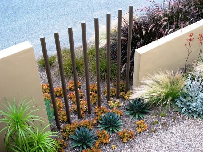 An expanse of solid wall can be opened up effectively by a short run of spaced verticals, as was done with these metal rods. The wandering border plants here reinforce the connection between outside and in.