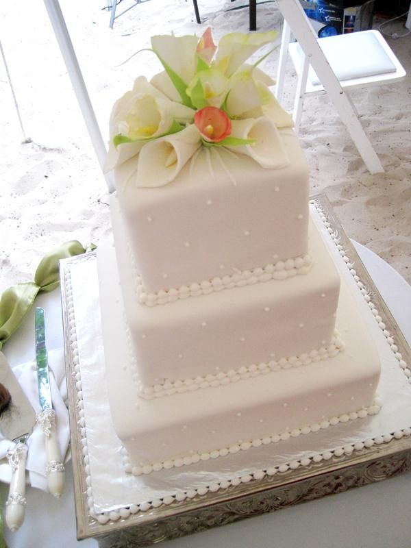 White wedding cake topped with calla lillies