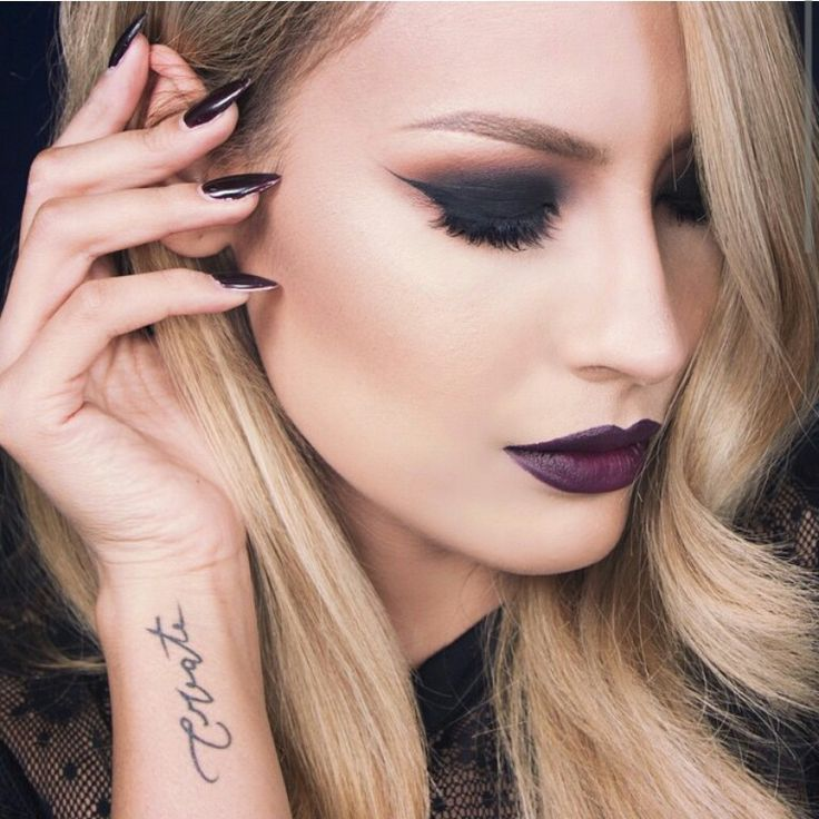 BLACK -- Amazing black smokey eye with a warm crease, winged liner (to add structure) and deep purple lips. Notice the skin is quite minimal as are the brows. Perfect balancing of the makeup look.