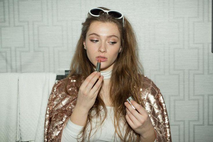 Sad and applying lipstick