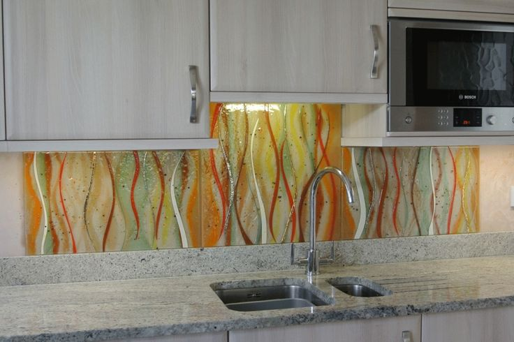 This particular piece was commissioned for a home in West Yorkshire, where this bespoke fused glass art splashback features. Most importantly, our wave design can be seen on each of the three sections. Although it is laid out as a triptych, it features in a kitchen and as such can be seen between the counter-tops and cabinets. The hues are bright and colourful and blend in somewhat with the lighting of the room.