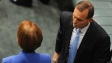 Tony Abbott walks past Julia Gillard