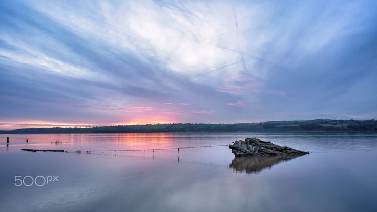 Purton Shipwreck Hulks at Blue Hour - Shot at blue hour in high tide the Purton Hulks, a mile-and-a-half-long stretch of ghostly boat wrecks that once formed the oddest of makeshift tidal erosion barriers on the River Severn.  The Purton Hulks is UK's largest ship graveyard.