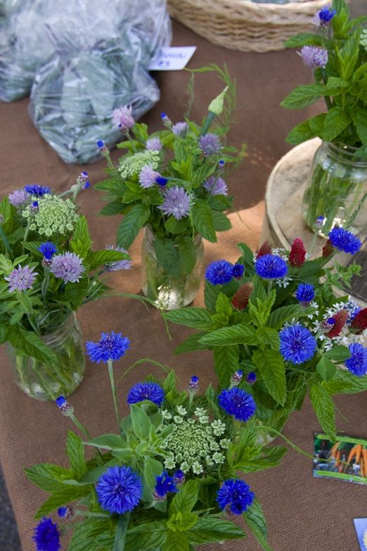 Dreaming of a down-to-earth early summer wedding with jam jars of flowering chives, mint, and cornflowers | The Natural Wedding Company