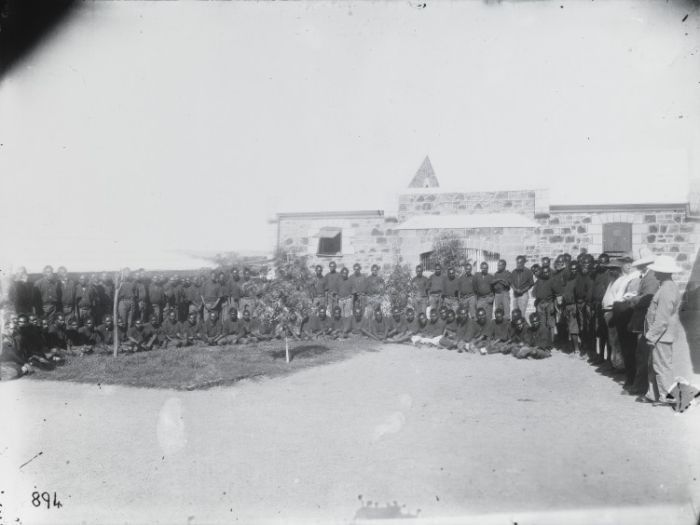 IMAGE: ABORIGINAL PRISONERS IN THE COURTYARD OF THE ROTTNEST ISLAND PRISON CA. 1883 (STATE LIBRARY OF WESTERN AUSTRALIA, 6968B)