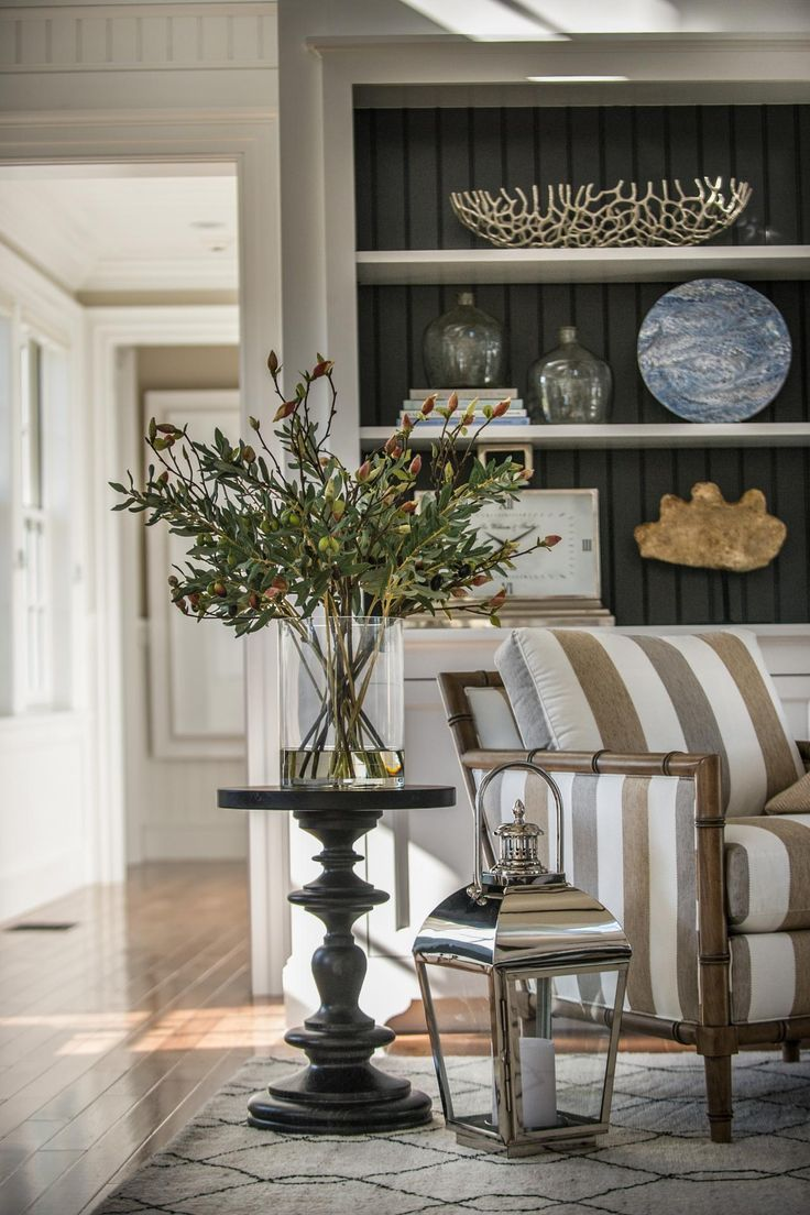 love the table, the huge vase of greenery, the striped chair, the back-painted wall of the shelves.....