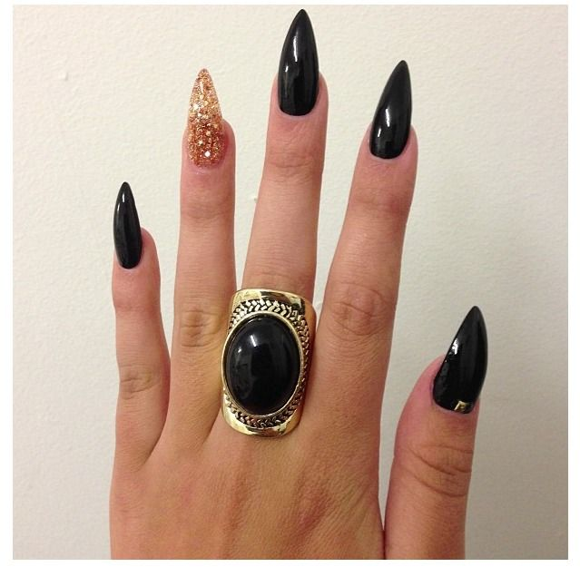 Black with ring finger gold glitter stiletto nails.