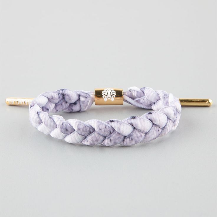 Rastaclat braided shoelace bracelet. Enamel plated metal adjustable cylinder & aglets featuring debossed emblems. Imported.