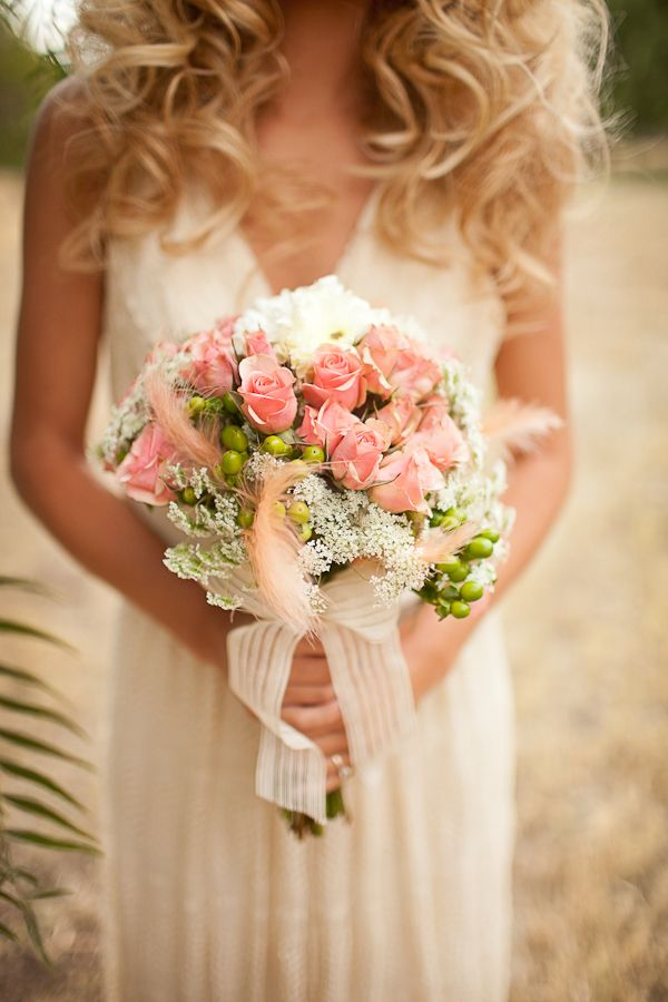 Those soft pinks, corals, ivory add a romantic touch to this #boho wedding inspiration. She added those pretty peach feathers and hypericum berry stems to add a modern twist to the traditional bouquet! #modernboho #bohemian