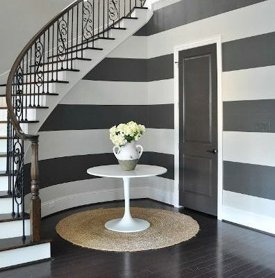 In a smaller hallway, paint horizontal stripes on the walls to make it feel longer, using contrasting colours such as blue and white, or brown and beige for a calming vibe. Read more tips for decorating your hallway here: https://nyde.co.uk/blog/decorating-a-hallway/