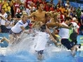 Britian's Tom Daly is thrown in the pool by the rest of his diving team after winning Bronze in the 10 meter platform