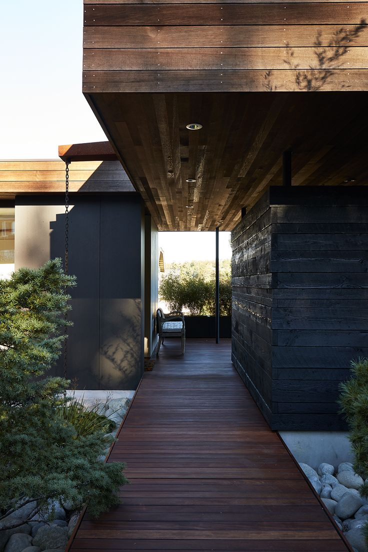 """Generous breezeways, walkways, and overhangs frame views beyond: """"It's like a promenade, with a forest at the end of the road,"""" says Deb."""