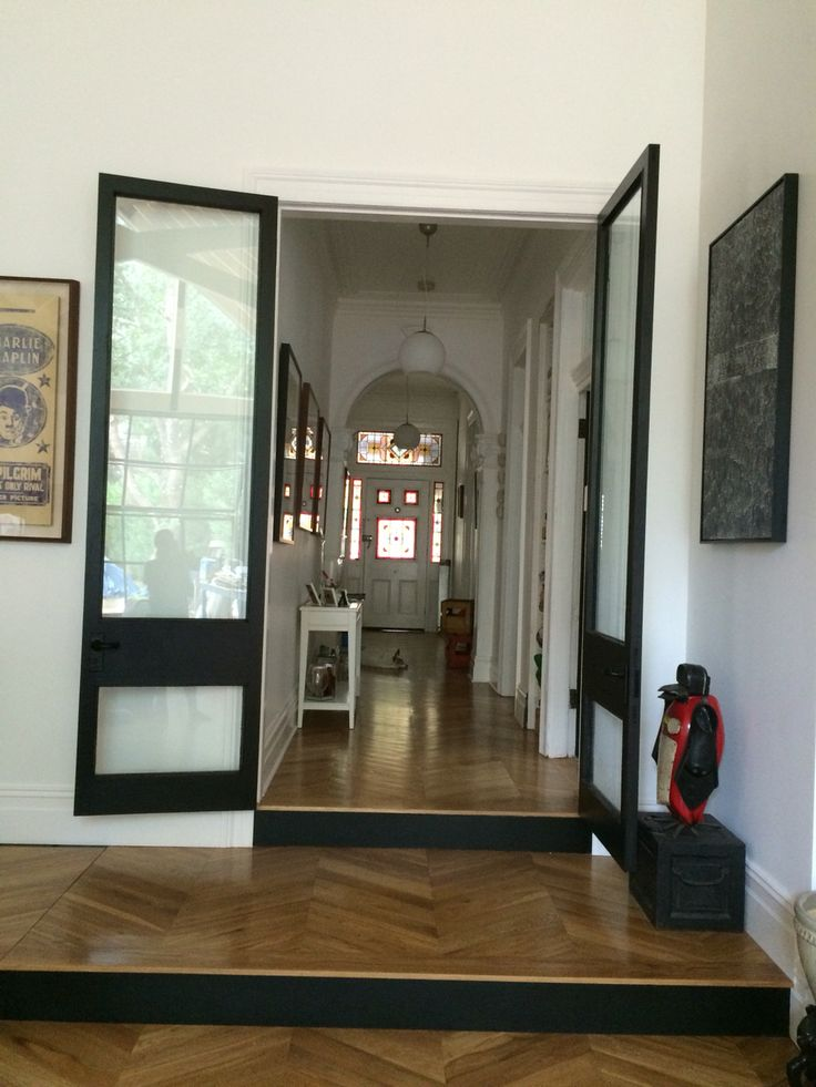 Hallway of original house meets new open plan. Oversized doorway cut thru and suppressed doors for a grand entry to the new area