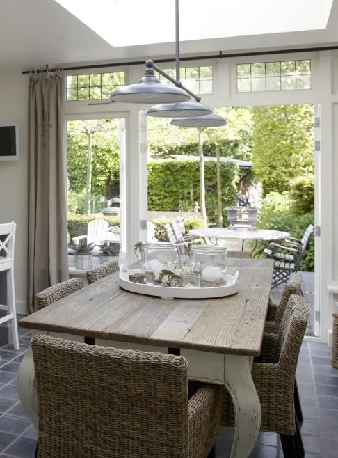 rustic top to the French inspired dining table - metal 'factory' lights and rattan chairs