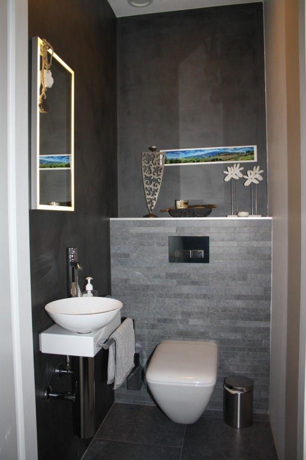 Gasten WC met grijze tegels, twee muren met DIVISORIO (betonlook) en 1 muur wit geverft.