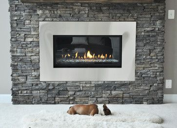 In front of this modern stone fireplace is the perfect place to take a nap.