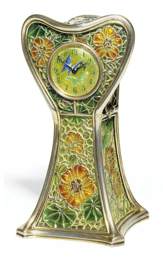 AN ART NOUVEAU ENAMEL AND SILVER-GILT TABLE CLOCK, BY EUGÈNE FEUILLÂTRE.  The yellow enamel dial with green Roman numerals and two butterflies adorning the centre, to the orange and green partially foiled and plique-à-jour enamelled floral case and sculpted foliate silver gilt top and reverse, with keywound brass movement, circa 1900, 16.4 x 8.3 cm, with French assay mark for gold and silver.  Case signed by Feuillâtre, movement signed by Lépine, no. 28962
