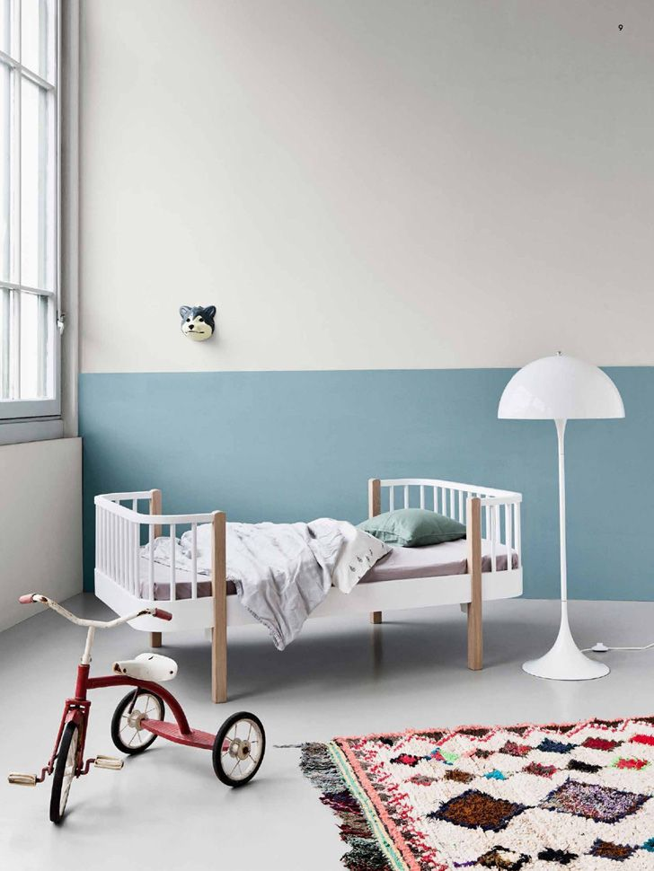 Half wall painted in blue + A kids room with personality: white bed + Moroccan rug