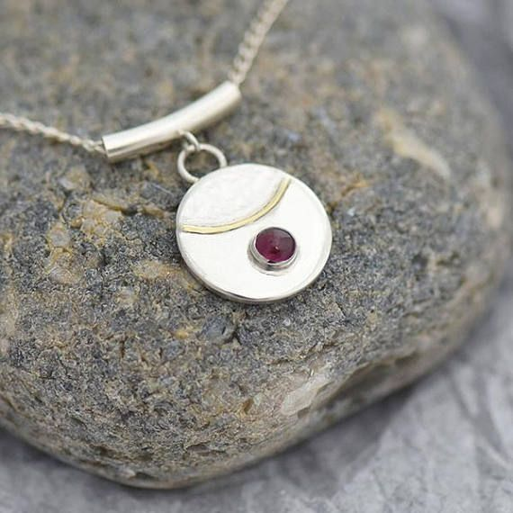 Garnet Jewelry : - Garnet pendant - Handmade Garnet Pendant – Stylish small round disc in sterling silver with cabochon stone and 18ct gold decoration above which the disc has a subtle hammered texture. Stone: Garnet Stone size: 4mm Pendant disc diameter: 15mm Pendant finish: satin, part hammered Includes silver chain necklace 44cm, 18 inch Garnet is the birthstone for January This piece is supplied in a black cardboard box for ease of storage, presentation or gift wrapping. It would make…