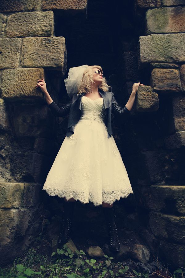 32-bride-posing-32-stone-wall-short-wedding-dress-lacy-biker-jacket