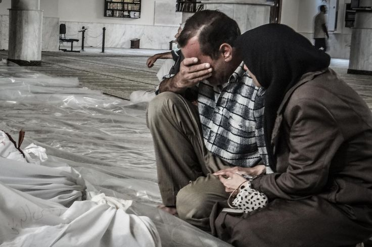 A mother and father weep over their child's body in Damascus suburb of Ghouta - Erbin News/NurPhoto/REX